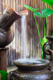 Water drop from clay jug in natural garden to thai style antique Stock Photos