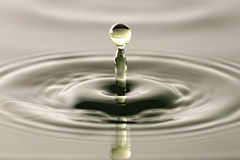 Water drop close up into a beautiful shape. Stock Image