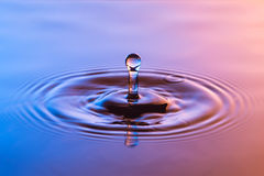 Water drop close up with concentric ripples colourful blue and a Royalty Free Stock Images