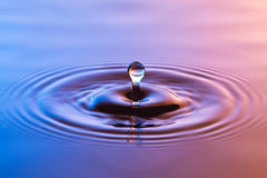 Water drop close up with concentric ripples colourful blue and a Royalty Free Stock Image