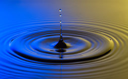 Water drop close up with concentric ripples colourful blue and y Royalty Free Stock Photos