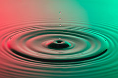 Water drop close up with concentric ripples colourful red and gr Stock Images