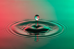 Water drop close up with concentric ripples colourful red and gr Royalty Free Stock Image