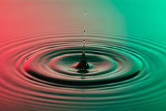 Water drop close up with concentric ripples colourful red and gr Royalty Free Stock Images