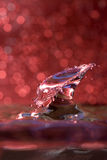 Water drop collision against a red background Royalty Free Stock Photos