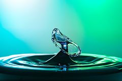 Water drop collision close up image with a green and blue background Royalty Free Stock Photos