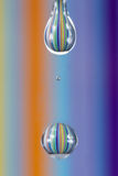 A water drop with colourful stripes reflecting from background m Royalty Free Stock Image
