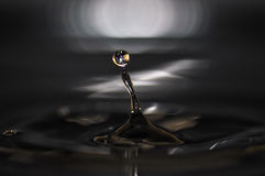 Water drop. Creating waves and ripples in on a dark grey background Royalty Free Stock Photography