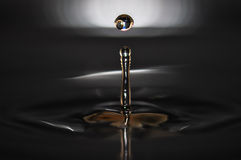 Water drop. Creating waves and ripples in on a dark grey background Royalty Free Stock Photo