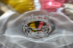 Water drop crown. With pink and yellow background stock photos