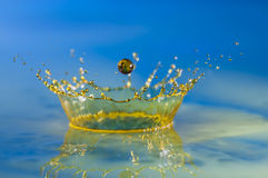 Water-drop crown. A yellow colored Water-drop splash with blue background stock photos