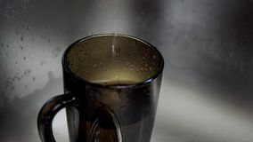 Water drop dripping. Water from the tap drips into the cup stock video