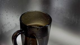 Water drop dripping. Water from the tap drips into the cup stock video footage