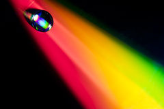 Water drop. On dvd disk. Multi colored background, like a rainbow Stock Photos