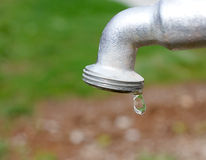 Water drop falling from metal gray tap Royalty Free Stock Images