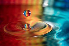 Water drop falling into water. With a colorful background stock photo