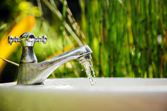 Water drop from faucet Stock Images