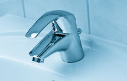 Water drop from faucet. Water flow from chromed steel faucet Royalty Free Stock Image