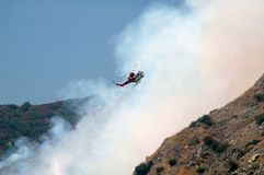 Water Drop Helicopter. Helicopter climbing after water drop in fight with forest fire in Southern California Stock Images