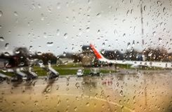 Water drop on mirror window of airplane. In rainy day while landing at airport with blur aircraft outside. Safety in transportation and travel concept stock photography
