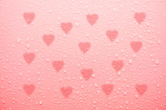 Water drop on pink love surface Royalty Free Stock Photo