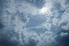 Water drop of rain on a glass, blurred blue sky and cloud in background, selective focus Royalty Free Stock Photos