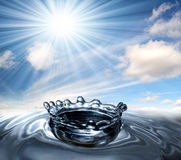 Water drop splash crown. Water crown with a sky, clouds and sun Stock Photo