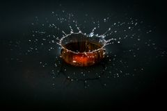 Water drop splash in a glass, black backgrounds. Water drop splash with black backgrounds stock photography