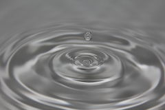 Water Drop Suspended Over Gray Water Royalty Free Stock Photos
