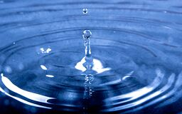 Water Drop on to Calm Water Causing Wave Effect royalty free stock image