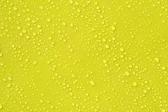 Water drop on yellow background. Stock Image