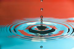 Water Droplet. Close-up of water droplet reflected on orange and cyan background stock images