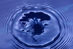 Water droplet. Blue water droplet emerging out of the water Royalty Free Stock Photography