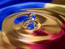 Water Droplet. Macro. The background consists of three stips of color papers placed at the bottom of a glass bowl royalty free stock photos