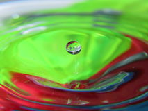 Water Droplet. Macro, the background consists of 3 colored cloth pegs placed at the bottom of a glass bowl Royalty Free Stock Photo