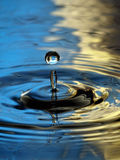 Water Droplet Ripple blue yellow column drop Royalty Free Stock Photo