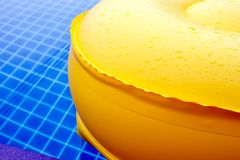 Water droplet on surface of vivid yellow pool float royalty free stock image