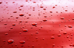 Water drop. Let texture on red surface royalty free stock image