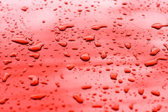 Water drop. Let texture on red surface Royalty Free Stock Photos
