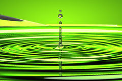 Water droplet and waves over green Stock Photo