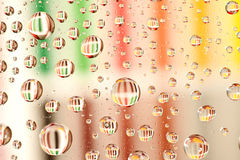 Water droplets as  lenses over a background. Royalty Free Stock Photography
