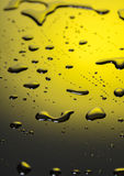 Water droplets on black-and-yellow plastic Royalty Free Stock Images