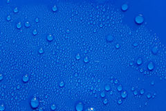 Water droplets on a blue plastic. Stock Image