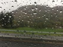 Water droplets forming on a car window. During a heavy storm royalty free stock photo
