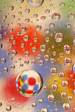 Water droplets on glass. Water drops on glass with a colorful background made of circles stock image