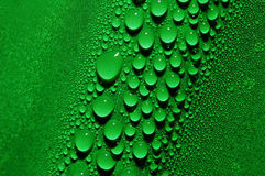 Water Droplets in Green. Water droplets of varying sizes produced by condensation on a green beverage bottle royalty free stock photo