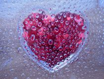 Water droplets with heart underneath. Hundred of water droplets were sprayed on clear surface with red heart shape underneath it Royalty Free Stock Image