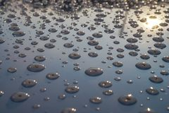 Water droplets on metal reflecting the sun royalty free stock image