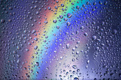 Water droplets. On a rainbow background stock photography