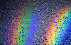 Water droplets. On a rainbow background royalty free stock photography